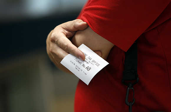 A man holds a slip of paper with the queue number as he waits to speak with an official inside the Income Tax office in New Delhi.