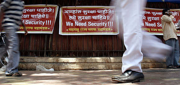People walk past placards during a demonstration by jewellers and workers in Mumbai. Thousands of jewellers shut their stores and held a protest against a rise in burglaries and attacks on gold merchants.