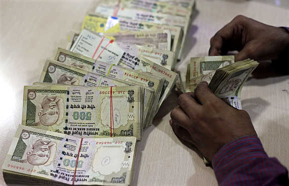 An employee counts currency notes at a cash counter inside a bank in Mumbai.