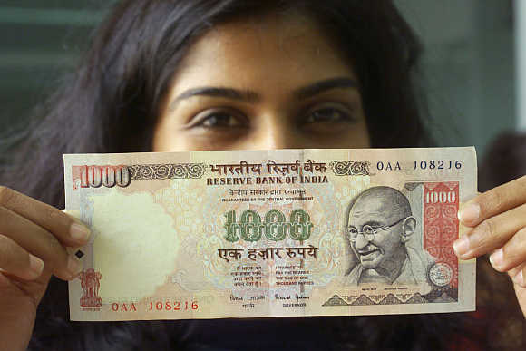 A girl displays a Rs 1,000 note in Mumbai