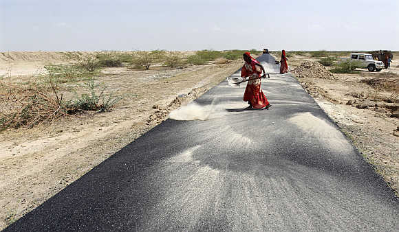 Women labourers throw dust on a road tarmac under construction at Bharadva village in Gujarat.