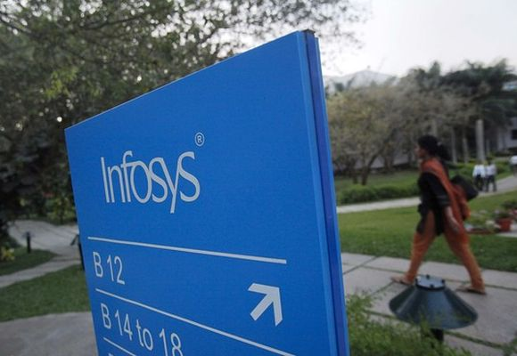 An employee walks past a signage board in the Infosys campus at the Electronics City IT district in Bangalore.