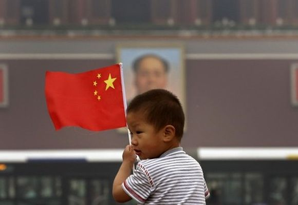 A child holds a Chinese national flag in front of a portrait of China's late Chairman Mao Zedong.