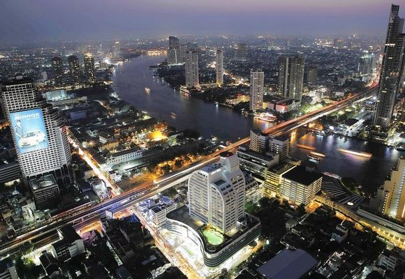 Cars and trains move on Taksin bridge over Chao Phraya river in central Bangkok, Thailand.