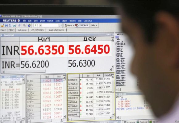 A currency trader works in front of a screen showing the value of the Indian Rupee against the US Dollar.