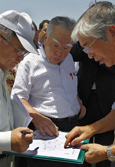 Suzuki Motor Corp Chairman Osamu Suzuki (C) and outgoing Chief Executive Officer of Maruti Suzuki India Shinzo Nakanishi (R) check a map at the construction site of a Maruti Suzuki plant at Vitthlapur village in Gujarat.