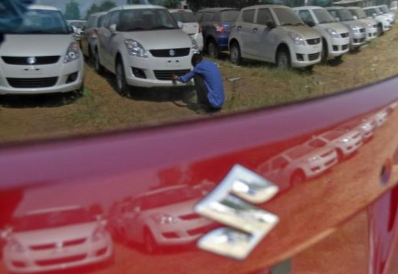 A worker cleans a Maruti Suzuki Swift Dzire car as he is being reflected on a car at the company's stock yard at Sanand, Gujarat.