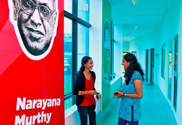 Employees talk as they stand next to flex board poster of Infosys founder Narayana Murthy at the Start-up Village in Kochi.