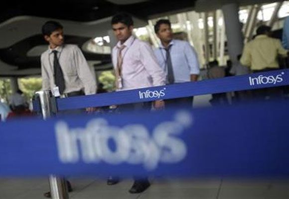 Employees of software company Infosys walk past Infosys logos at their campus.
