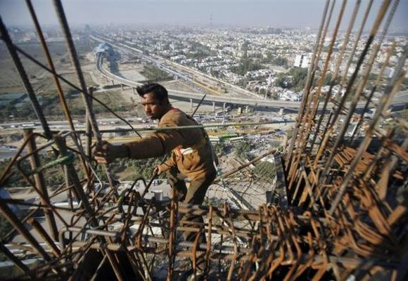 A labourer works at the construction of a residential complex at Noida.