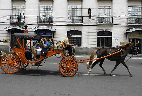 Tourists ride on a 'Kalesa', a horse drawn carriage, in Manila's historic Intramuros also known as 'Walled city' in the Philippines.