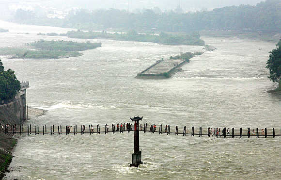 Visitors cross part of a 260-metre Anian cable bridge, one of five major bridges in ancient China, over Minjiang River at Dujiangyan, 50km north of Chengdu.
