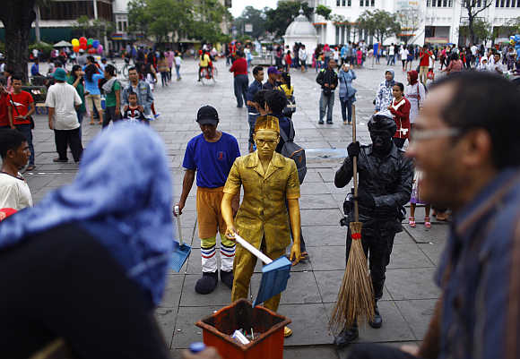Statue street performers pose as cleaning workers at Fatahilah museum park in Jakarta's old city in Indonesia.