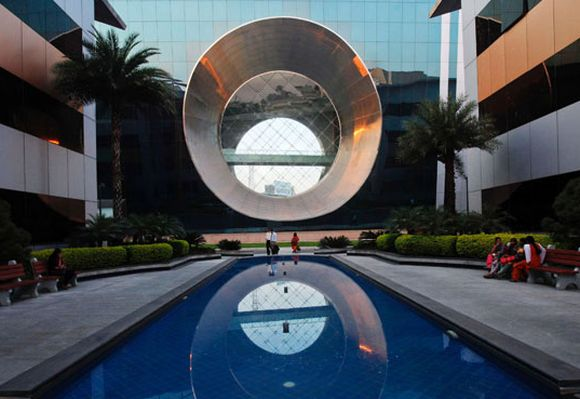 Employees walk in front of a building dubbed the ''washing machine'', a well-known landmark built by Infosys.
