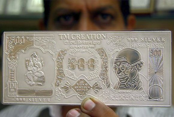 A jeweller displays a silver plate in the form of a rupee note.