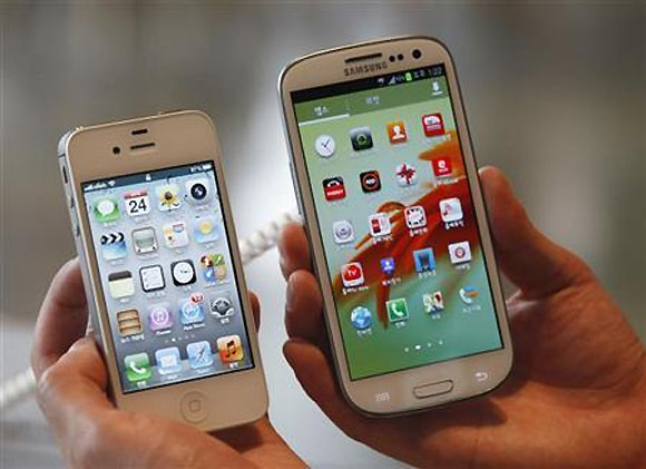 An employee poses as he holds Apple's iPhone 4s (L) and Samsung's Galaxy S III at a store in Seoul.