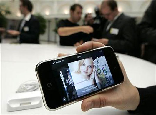 Journalists test an Apple iPhone.