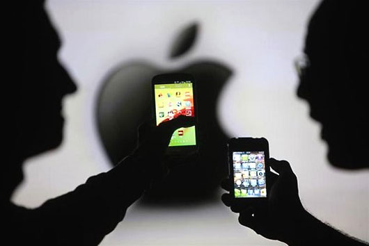 Men are silhouetted against a video screen as they pose with Samsung Galaxy S3 and iPhone 4 smartphones.