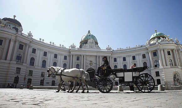 A Fiaker horse carriage passes Hofburg Palace in Vienna, Austria.