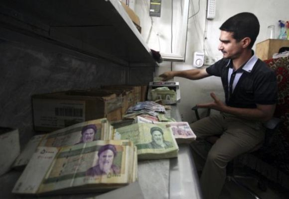 Man counts stacks of Iranian rials using a money-counting machine.
