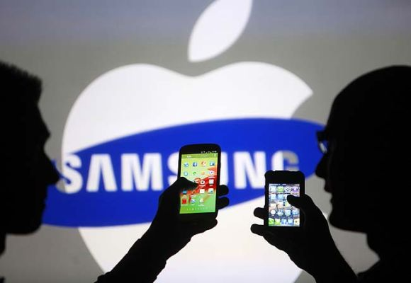 Men are silhouetted against a video screen as they pose with Samsung Galaxy S3 and iPhone 4 smartphones in this photo.