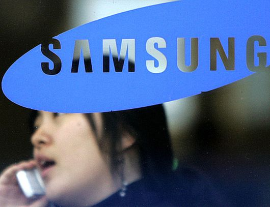 A woman uses her mobile phone behind a logo of Samsung Group in Seoul.