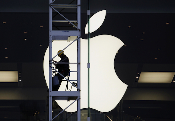 A worker climbs outside an Apple store in Hong Kong.