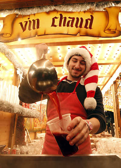A vendor serves hot wine at the traditional Christkindelsmaerik (Christ Child market) near Strasbourg Cathedral in France.