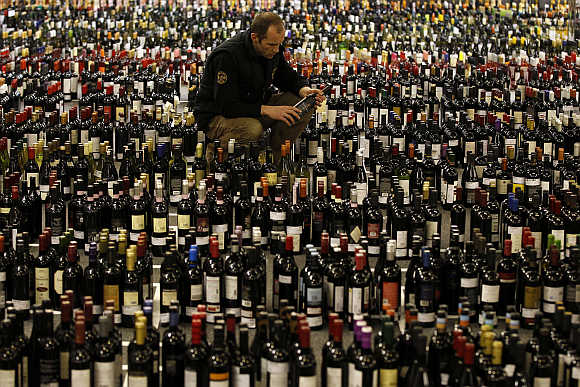 A man looks at a label among wine bottles waiting to be tasted at the International Wine Challenge in London.