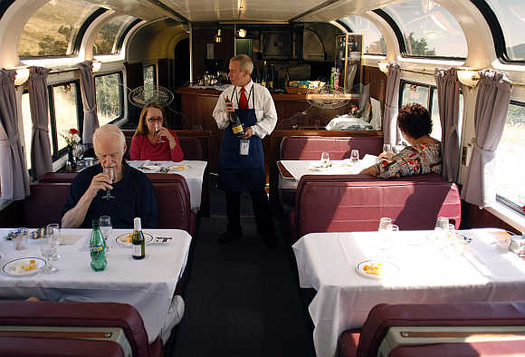 Amtrak train attendant Richard Newberry serves wine to passengers aboard the Coast Starlight Amtrak train in California.