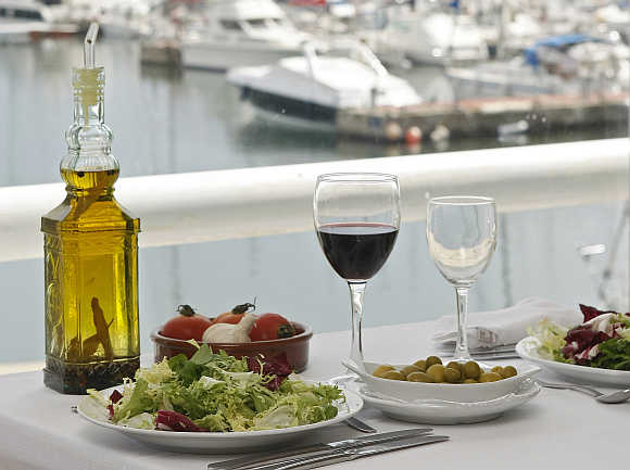 A glass of wine rests on a table at the port of El Masnou, near Barcelona, Spain.