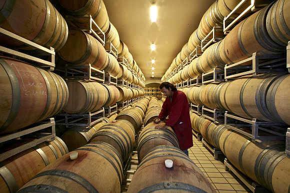 Giancarlo Bonci checks a wine barrel in the cellar of the Arnaldo Caprai vineyard near the Umbrian town of Montefalco in Italy.