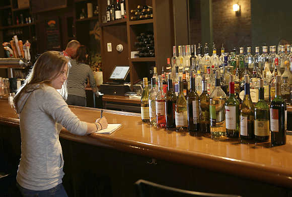Manager Maggie Brown takes inventory of bottles of wine at the Globe Restaurant on Boylston Street in Boston, Massachusett, United States.