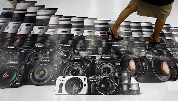 A woman walks on an advertisement for Canon digital cameras at an electronics retail store in Tokyo.