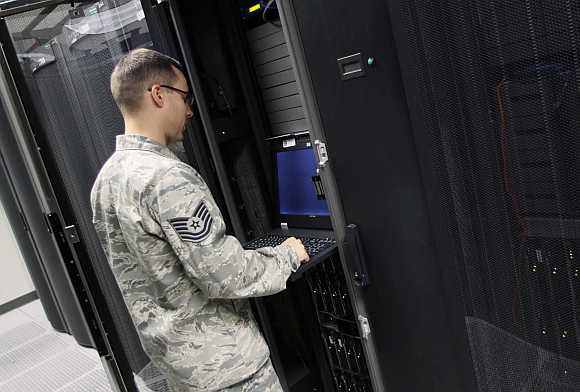 TSgt James Ortiz, shift lead, boundary protection looks over a rack in the server room at the Air Force Space Command Network Operations & Security Center at Peterson Air Force Base in Colorado Springs, Colorado.