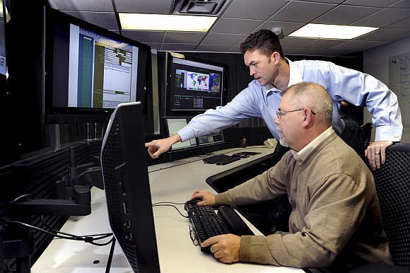 US Department of Homeland Security employees work on the Industrial Control Systems Cyber Emergency Response Team operational watch floor where they monitor, track and investigate cyber incidents at the Idaho National Laboratory in Idaho Falls, Idaho.