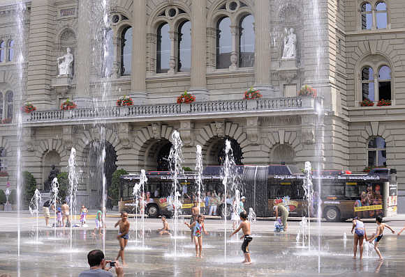 Children play in the fountain in front of the Bundeshaus, the seat of the Swiss parliament, in Bern.