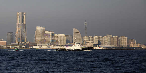 Ships sail against skyscrapers lining the background at Yokohama Bay in Yokohama.