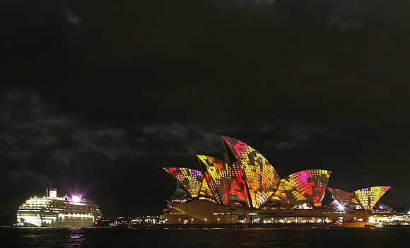 A cruise ship navigates past the Sydney Opera House as 'Play' by The Spinifex Group is projected on its sails as part of Vivid Festival in Sydney.