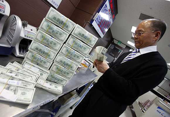 An employee of the Korea Exchange Bank counts one hundred dollar notes in Seoul, South Korea.