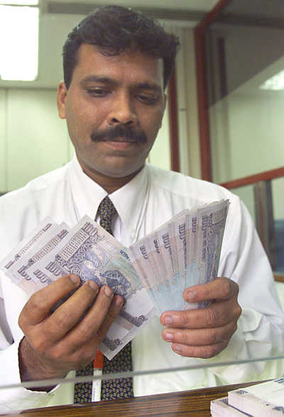 A bank employee counts hundred rupee notes in Mumbai.