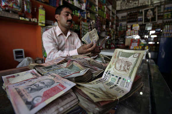 A shopkeeper counts currency notes inside his shop in Jammu.