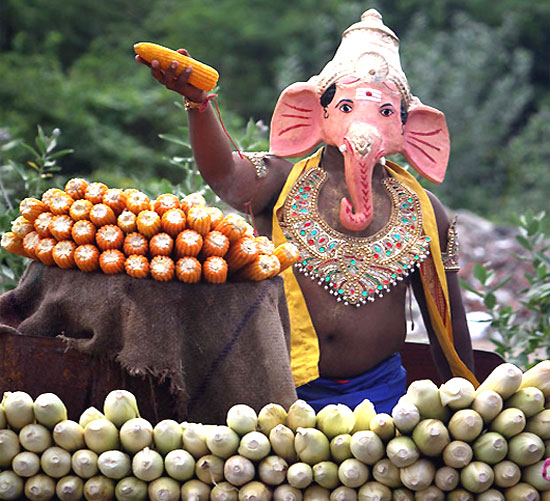 A man, wearing a mask of Hindu god Ganesh, the deity of prosperity, holds up a cob of corn at a roadside stall on the fourth day of the Ganesha Chaturthi festival in Chennai.