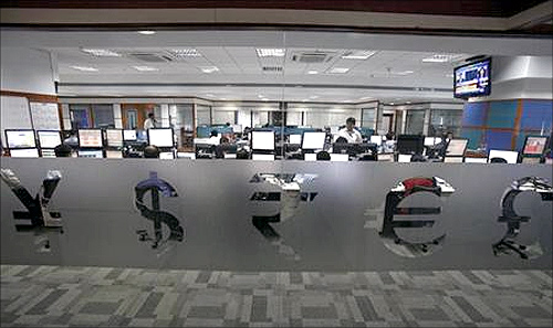 Foreign currency traders work inside a trading firm behind the signs of various world currencies in Mumbai.