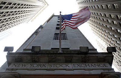 US flag waves in the breeze above one of the entrances to the New York Stock Exchange.