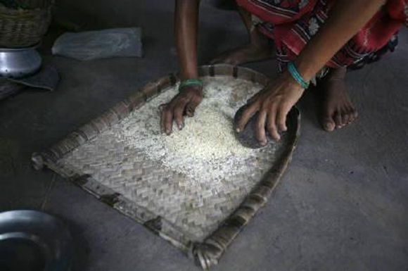 A woman sorts rice bought from a ration shop.