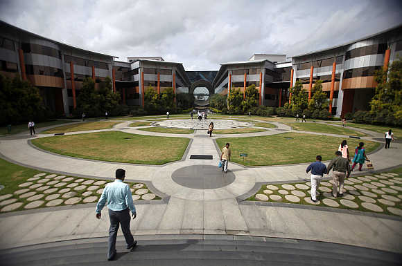 Employees walk in a forecourt at the Infosys campus in the Electronic City area of Bangalore.
