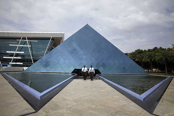 Employees walk in front of a pyramid-shaped building at the Infosys campus in the Electronic City area of Bangalore.