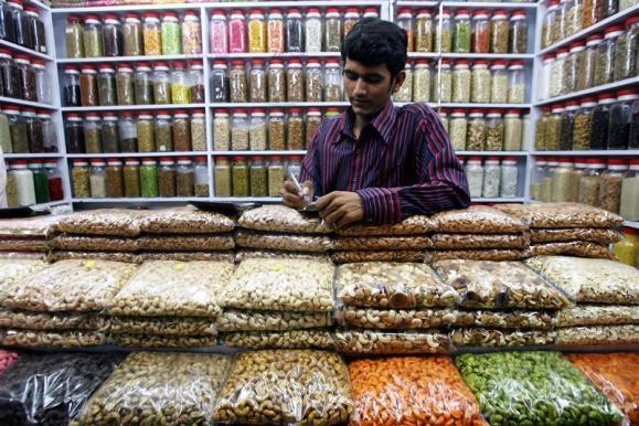 A shopkeeper does calculations standing in his nut and spice shop in Mumbai.