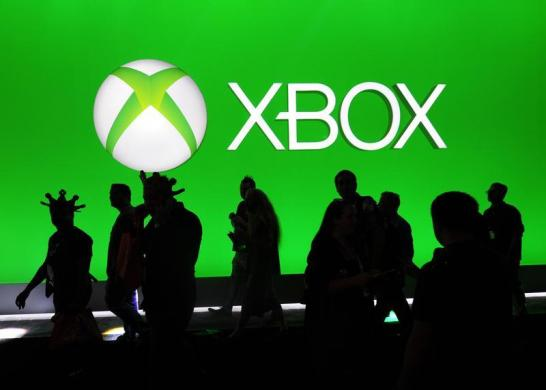 Convention goers pass the Xbox booth during E3 in Los Angeles, California.